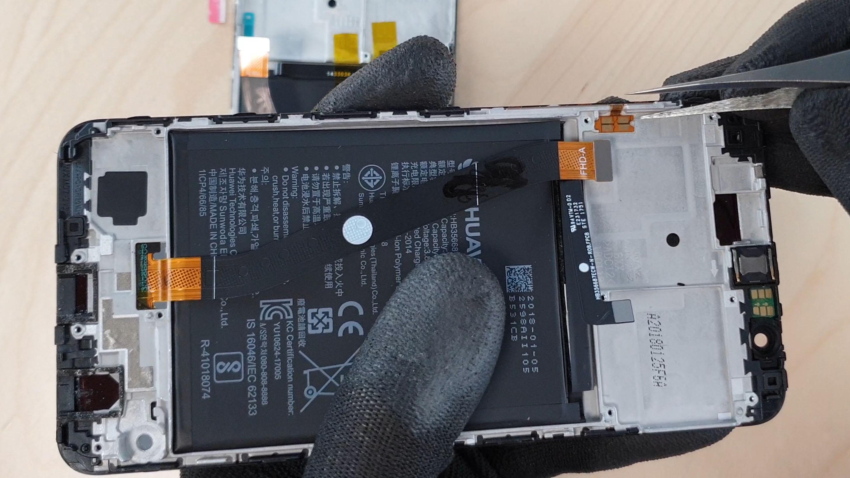 Le technicien enlève la nappe power/volume pour changer l'écran du honor 7x