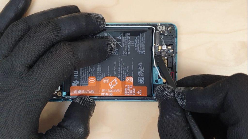 pour changer l'écran d'un Huawei P30 le technicien enlève la carte avec le connecteur de charge